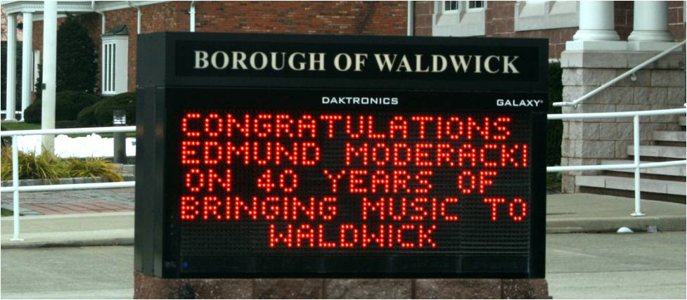 sign recognizing ed moderacki's 40 years as director